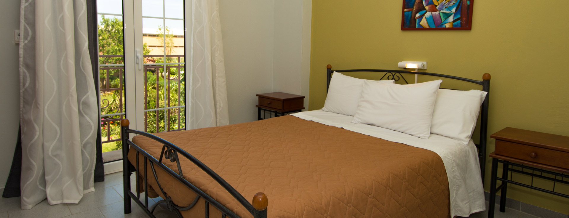 Room at Lemonia Accommodations with double bed and terrace with garden and sea view.